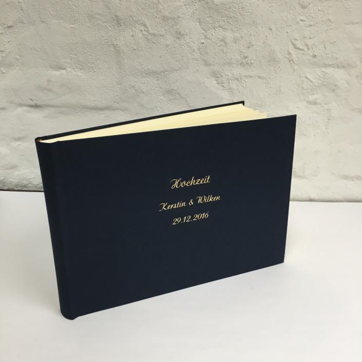 Rauchblaues Fotoalbum mit großer und kleiner Schreibschrift in Gold.