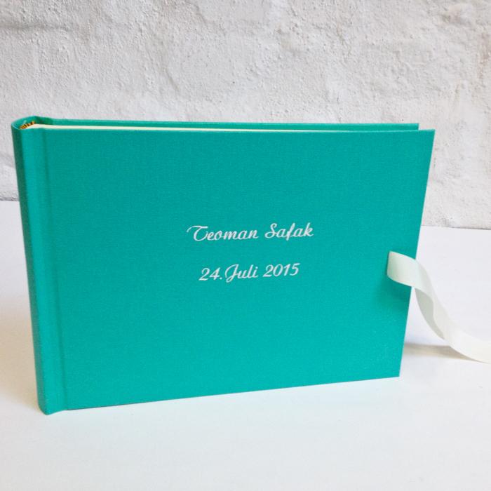 Kinderalbum mit weißer Prägung und weißer Schleife zu türkis pastell