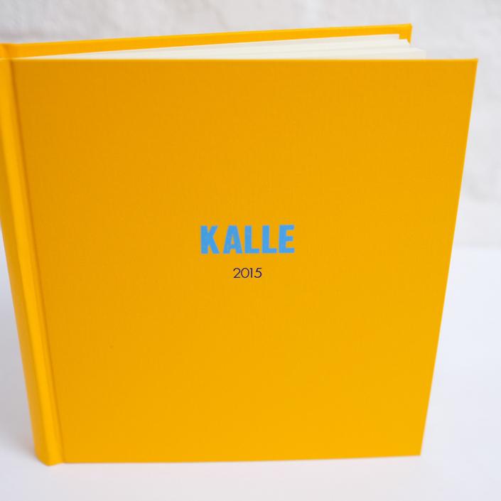 leuchtend gelbes Fotoalbum mit fetter Typo (letterpress Optik) in Hellblau und Futura in Dunkelblau