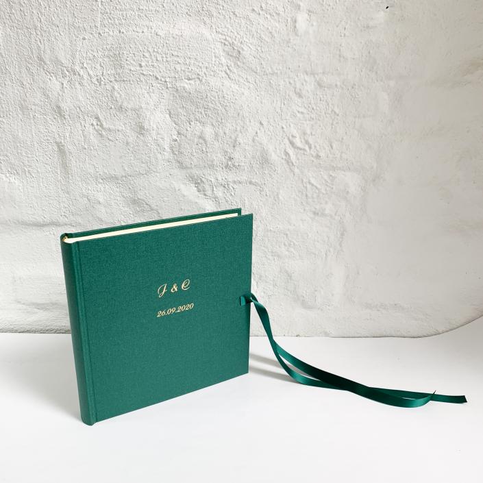 Große und kleine goldene Schreibschrift auf Waldgrün.