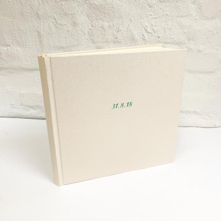 Perlweißes Hochzeitsfotoalbum mit grüner Schreibschrift, pur & schlicht.