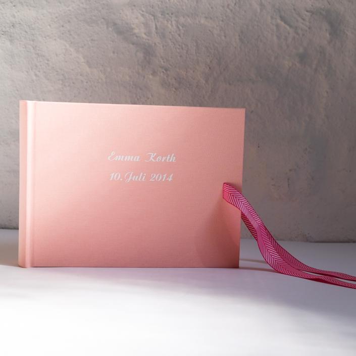 kleines zartrosa Album mit weißer Schreibschrift und Schleife