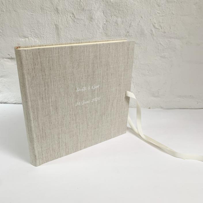 Rustikales Hochzeitsfotoalbum mit weißer Schleife und weißer Schreibschrift.