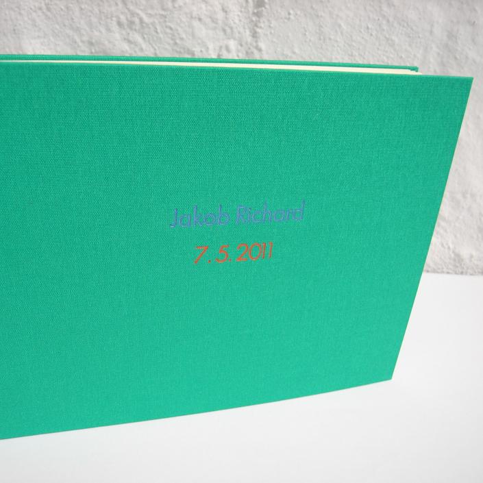grasgrünes Kinderalbum mit Prägung in Taubenblau und Rot