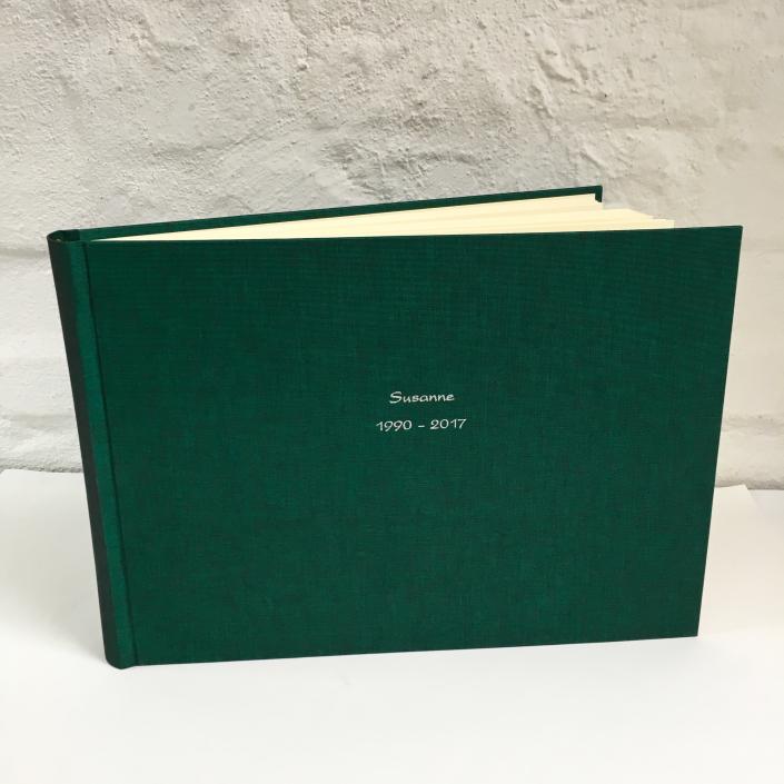 silberne Kartenschrift auf zweifarbig schimmerndem Dunkelgrün