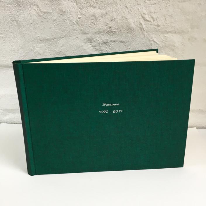 längliches dunkelgrünes Fotoalbum mit silberner Kartenschrift