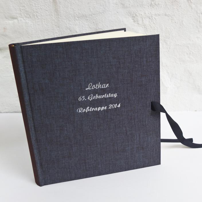 dunkelblaues Album mit zweifarbig schimmerndem Bezug und Prägung in Silber