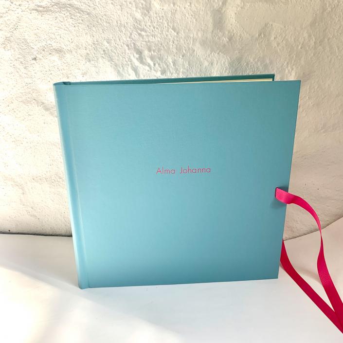 Hellblaues robustes Kinderfotoalbum mit pinker Prägung und pinker Schleife.