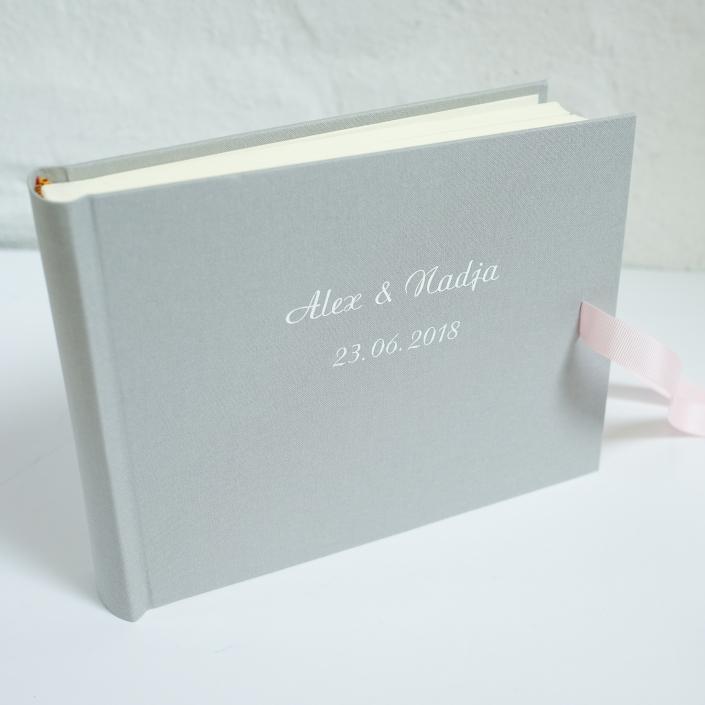 weiße Schreibschrift auf hellgrauem Leinen mit zartrosa Schleife