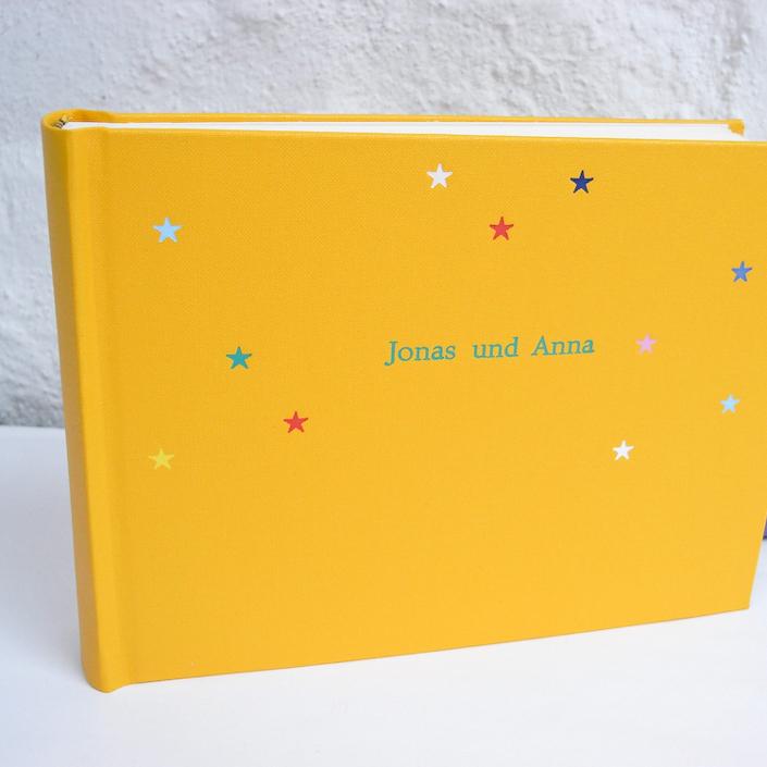grüne Times mit bunten Sternchen auf Gelb