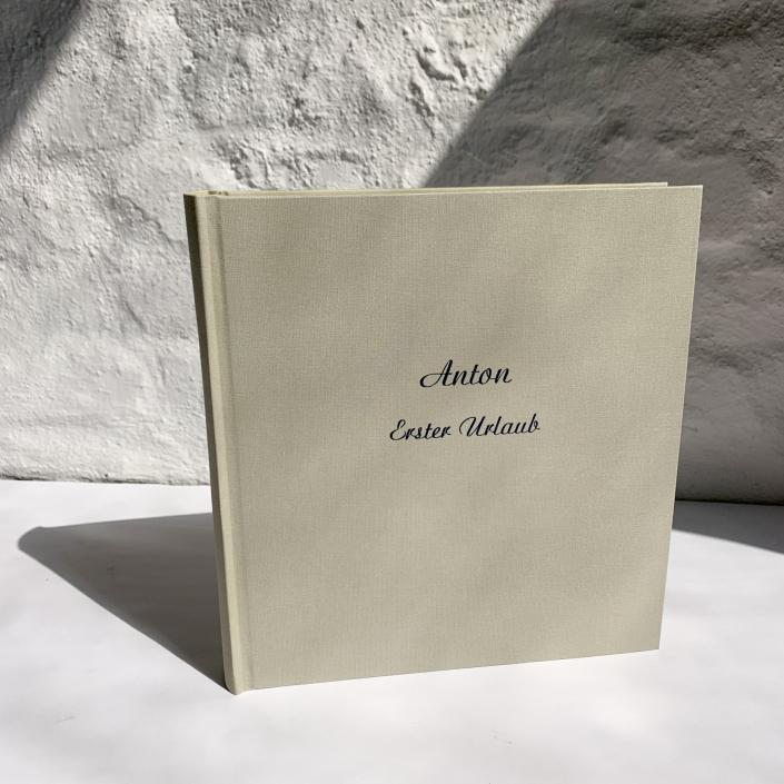 Blassgrünes Kinderfotoalbum mit dunkelblauer Prägung und großer Schreibschrft.