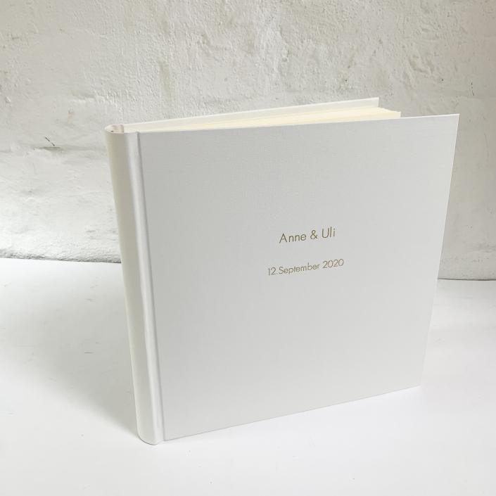 Weißes Fotoalbum in 31x31 mit goldener Futura in Groß und klein.
