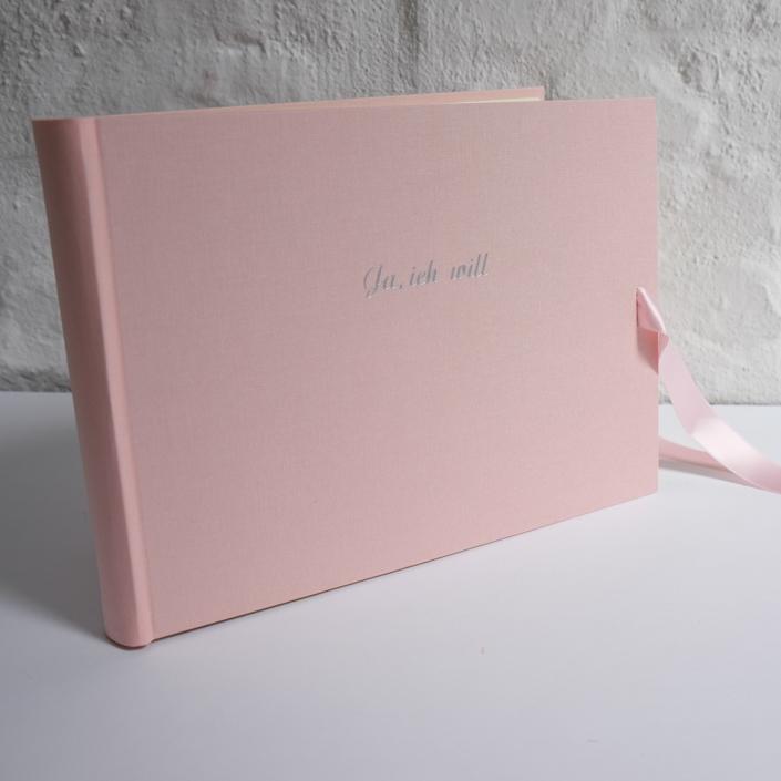 Große silberne Schreibschrift auf rosa Leinen. Format 24x35 cm