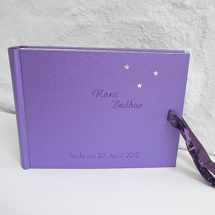 hell lila Album mit silbernen Sternchen, Samtschleife und lila Prägung in Schreibschrift und Futura