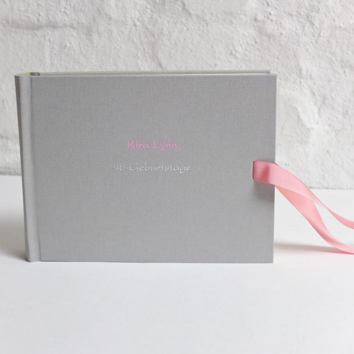 Kartenschrift in Rosa und Silber auf hellgrauem Leinen