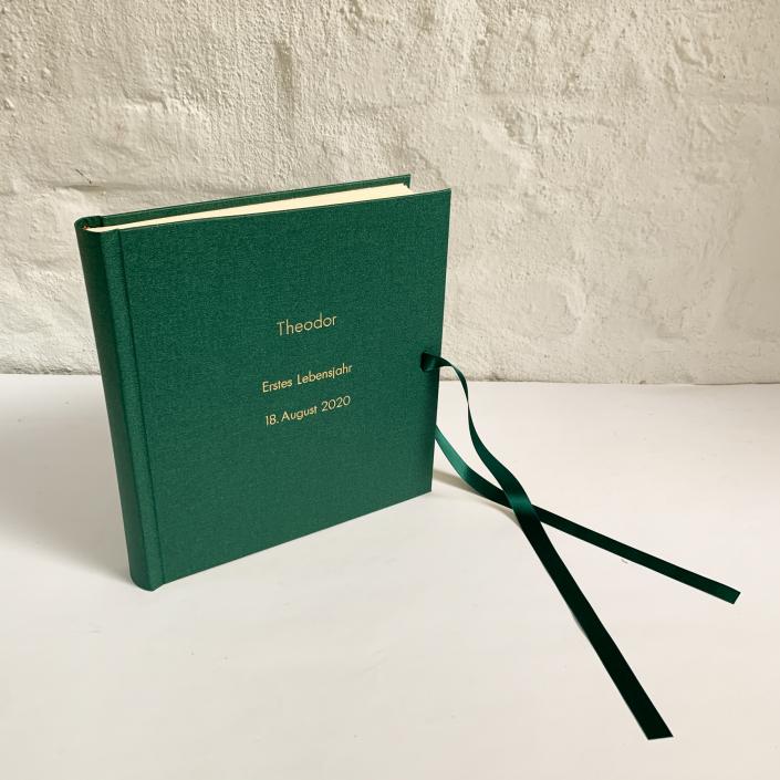Edles Kinderfotoalbum in Waldgrün mit kleiner und großer Futura in Gold und Schleife.